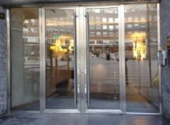 Bildet viser AXO Finans sitt pene inngansgparti. På høyre side er det ringeklokkesystem. Hele inngangspartiet er i glass med glass dører.