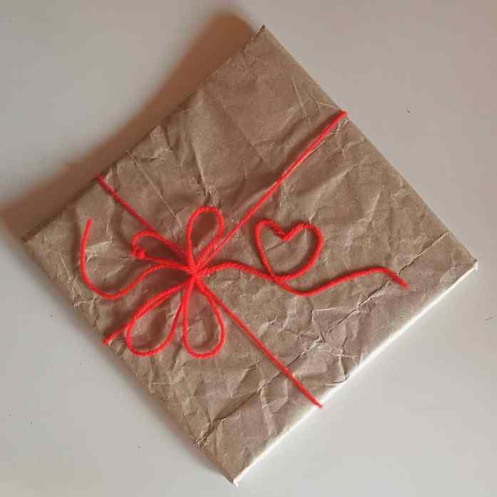 confezione regalo con cuore di lana rosso