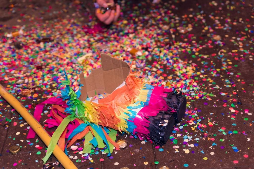 a piñata lays lifeless on the floor, with colorful confetti scattered all around.