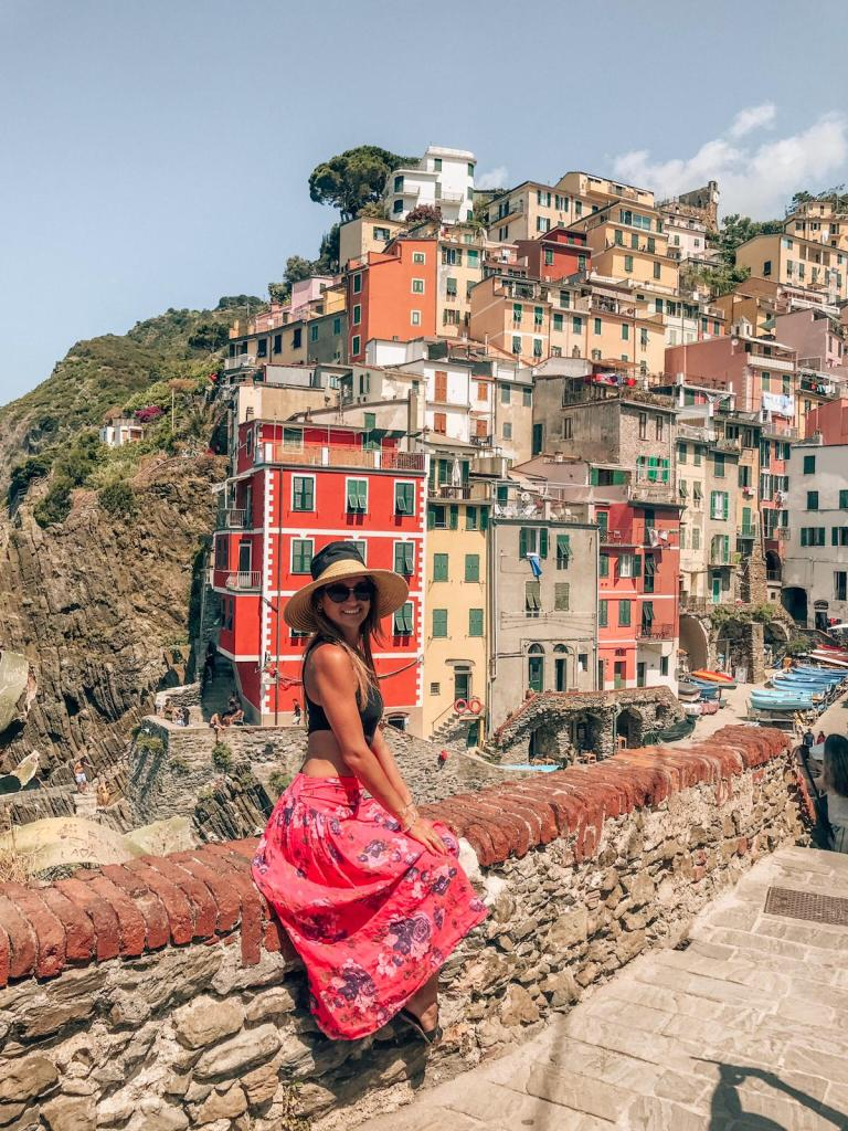 Girl sitting on a wall in Riomaggiore, Cinque Terre, during summer in Italy. Italian sumer photography in Cinque Terre. Get top tips to enjoy Cinque Terre and avoid common rookie mistakes while you travel  #cinqueterre #italy #whattodo #summerdestination #rookiemistakes