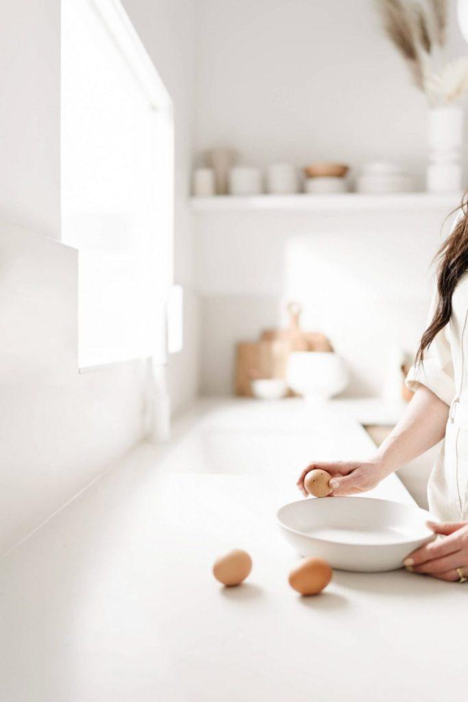 woman's hands preparing egg in a minimalist kitchen