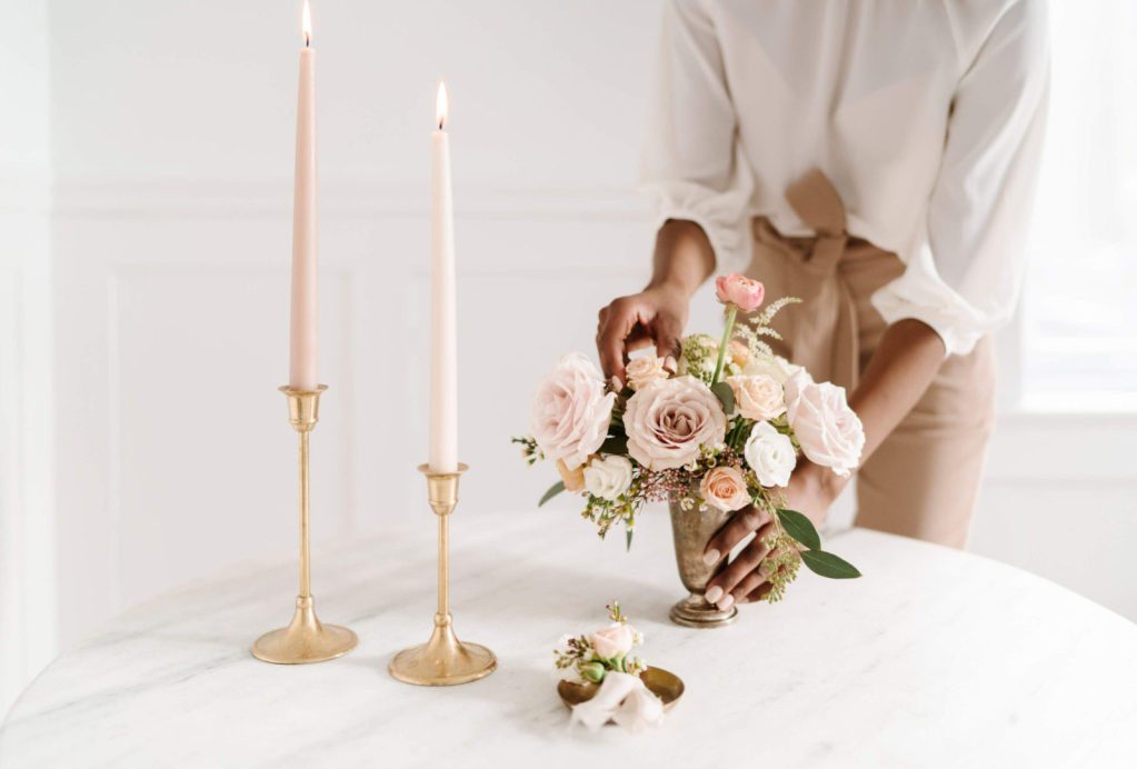 Woman dressed in neutral colors setting a beautiful flower arrangement on a table. Want to find out your personal style? Read my post and get helpful tips (and inspiration) on how to find and love your unique fashion style. Download for free my style sheet #personalstyle #wardrobe #classicfashion #minimaloutfits