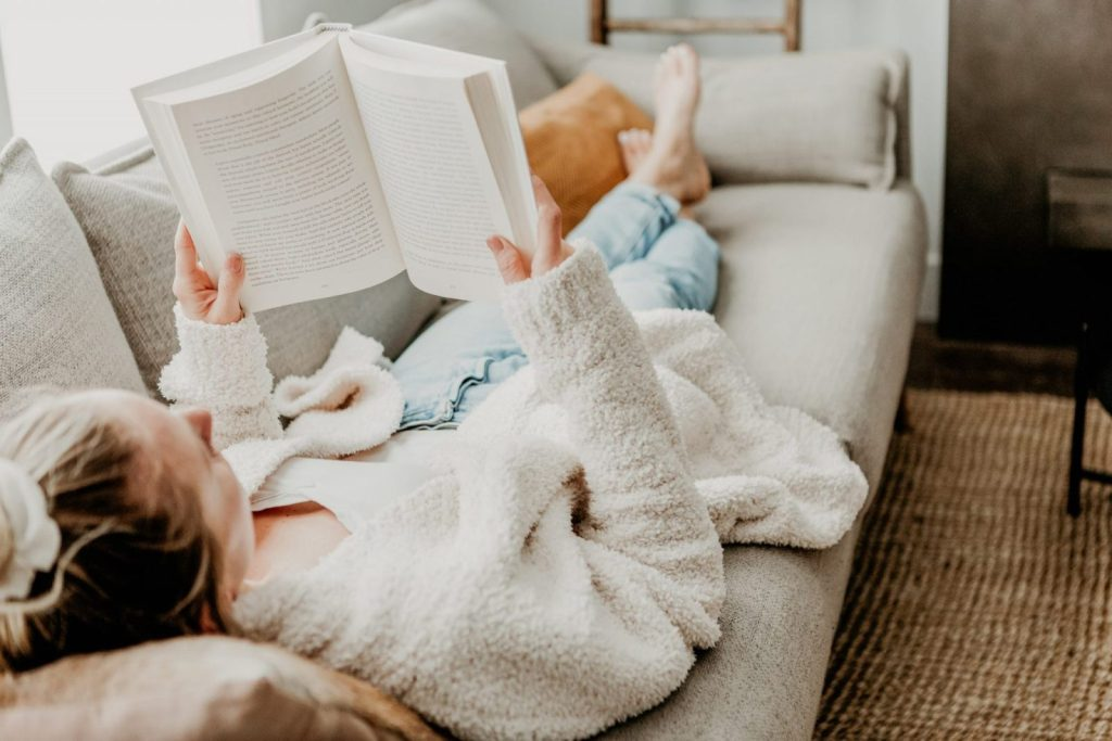girl laying down on a couch reading a book, with her hair in a piny tail. Feeling overwhelmed is a huge reason why I rebranded my blog