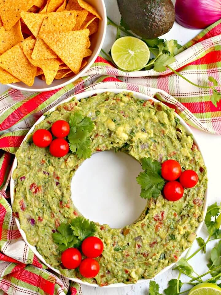 Guacamole Wreath | Want to serve your guests the best Christmas party appetizers this year? Find a list of 40+ Christmas appetizers ideas & easy recipes for Christmas party appetizers, both sweet and savory holiday food. From elegant Christmas finger food ideas to easy dips, and simple crockpot holiday appetizers, (vegetarian, keto and even gluten-free appetizer ideas), perfect for a crowd and for kids. #christmaspartyappetizers #appetizersforchristmasparty #christmasparty #fingerfood #christmasfood