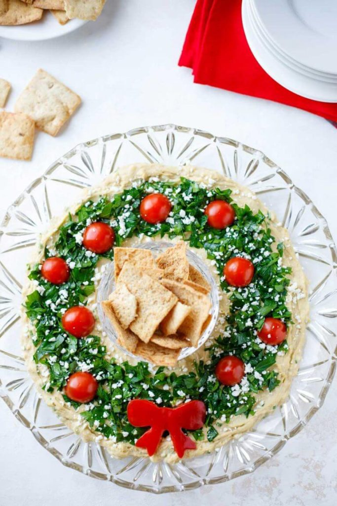 Hummus Wreath | Want to serve your guests the best Christmas party appetizers this year? Find a list of 40+ Christmas appetizers ideas & easy recipes for Christmas party appetizers, both sweet and savory holiday food. From elegant Christmas finger food ideas to easy dips, and simple crockpot holiday appetizers, (vegetarian, keto and even gluten-free appetizer ideas), perfect for a crowd and for kids. #christmaspartyappetizers #appetizersforchristmasparty #christmasparty #fingerfood #christmasfood