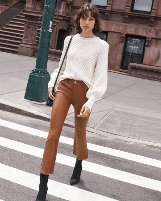 woman wearing a white blouse and camel high wasted pants
