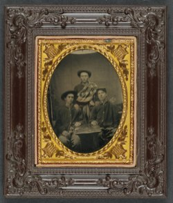 Three unidentified soldiers in front of painted backdrop showing 34-star American flag 1861