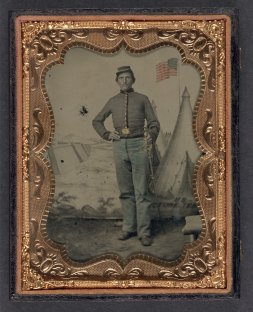 Unidentified soldier in Union uniform with cavalry saber in front of U.S. Picture Tent painted backdrop