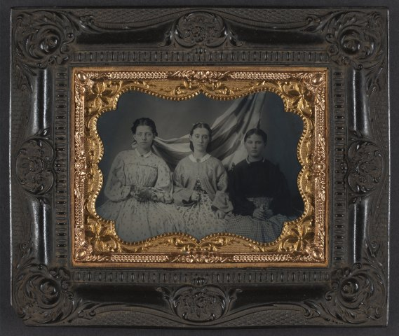 Unidentified young women in dresses in front of American flag 1860