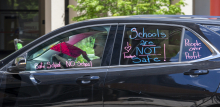 """A woman drives a car with the words """"Schools are not safe!"""" """"I love teachers"""" and """"People over profit"""" painted on the windows"""