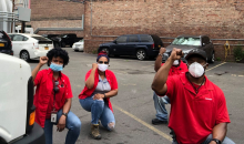 Four Black workers in red Verizon shirts kneel in a parking lot, fists raised.