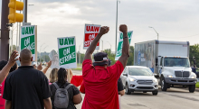 """Strikers shown from behind, waving at cars, fists in air, signs read """"UAW On Strike"""""""