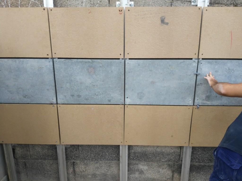 colocación de paneles de madera y piedra simulando una fachada transventilada