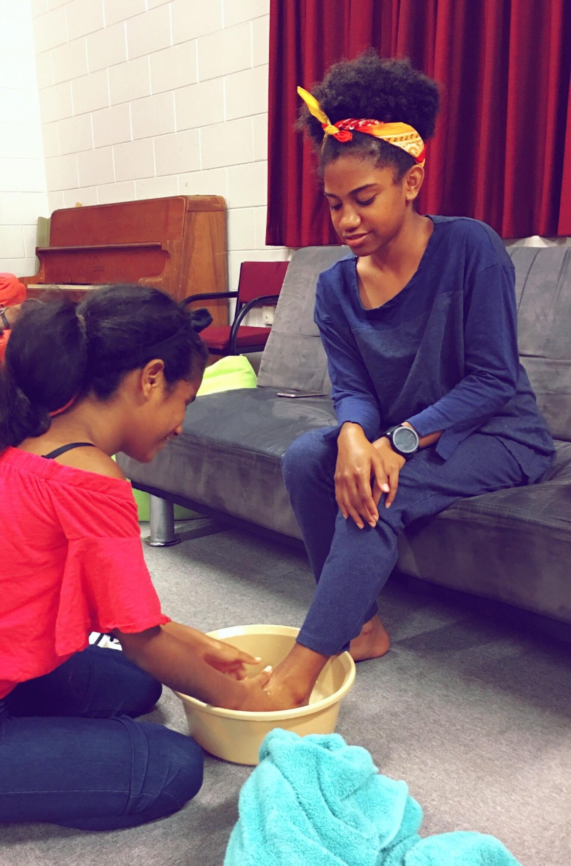 Foot washing during Friday night's worship. The girl sitting is Siunari'i Paiva, Y9, and the other is Molly Pokaran, Y10