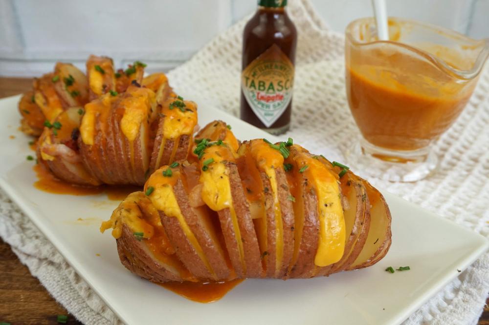 patatas hasselback con queso cheddar, bacon y salsa brava
