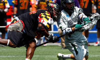 May 28, 2012; Foxborough, MA, USA; Loyola Greyhounds attack Eric Lusby (right) scores a goal while being checked by Maryland Terrapins long stick midfielder Goran Murray (left) during the first half of the NCAA Division I Men's Lacrosse National Championship at Gillette Stadium. Mandatory Credit: Mark L. Baer-US PRESSWIRE