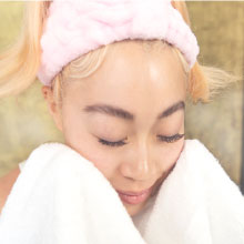 female wiping face with towel dry face