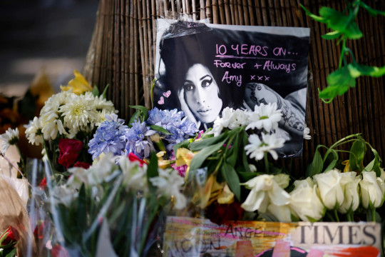 Amy Winehouse Fans Pay Tribute To Late Singer On 10th Anniversary Of Death   Amy Winehouse's family members and fans have gathered at the late singer's home in North London to pay tribute to her on the 10th anniversary of her death.  The musician died on July 23, 2011 at the age of 27 from alcohol poisoning.  Pictures have shown a temporary shine situated outside of her house, where supporters have left flowers, balloons and other memorabilia to show their love for Amy.  A group of fans also huddled together for a photo, as they posed with two posters which featured images of Amy alongside the words: '10 Years Without Amy'.  Messages of condolences were also left at the shrine by some, with many expressing their sadness at how long it has been since the singer has gone.  Other photos show fans standing alongside Amy's statue, which is situated in Camden Town.