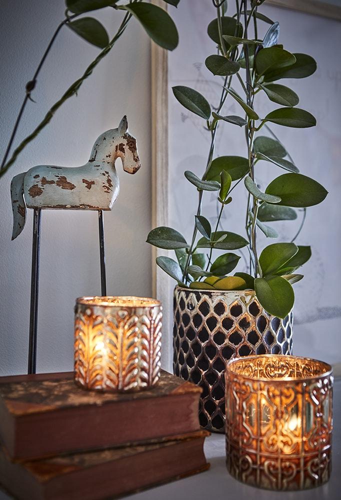 statuette de cheval vintage sur socle avec bougies et plante en pot
