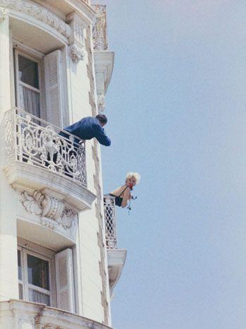 Le 11ème Festival de CANNES se déroule du 2 au 18 mai : vue en contre-plongée d'un photographe prenant en photo Jayne MANSFIELD souriante, une rose à la main, tous deux penchés à un balcon d'une chambre du Carlton lors du festival de Cannes en mai 1958.