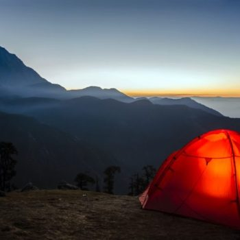 A tent on a mountain at sunset.