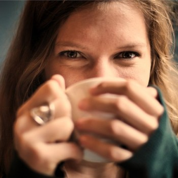 A woman drinking a cup of coffee.