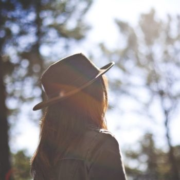 A woman with a hat in the woods.