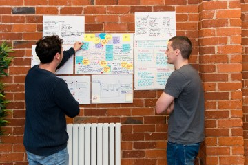Adam and John reviewing workshop notes on the wall