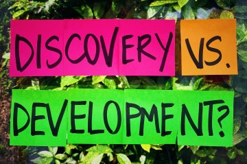 A set of post-it notes with the words discovery versus development written on them