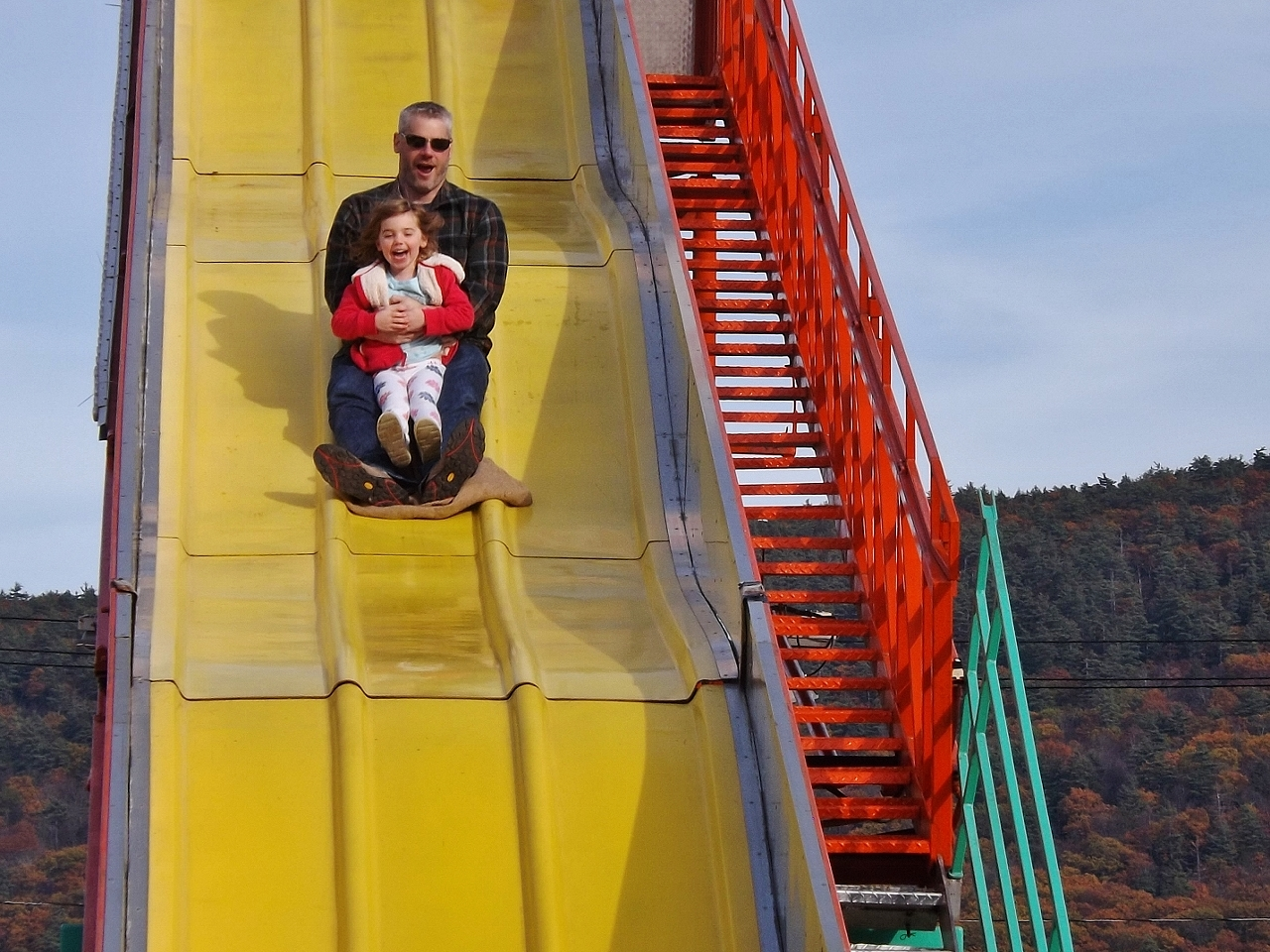 A giant slide provides a ride for this man and child.