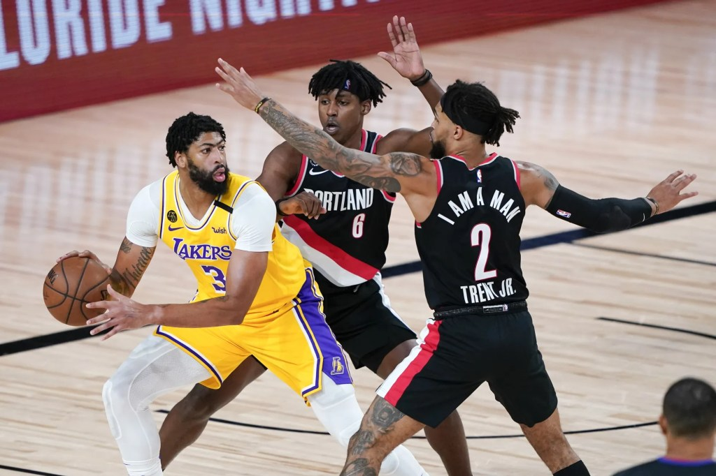 Los Angeles Lakers' Anthony Davis (3) looks for a way past Portland Trail Blazers' Jaylen Hoard (6) and Gary Trent Jr. (2) during the first half of an NBA basketball first round playoff game Saturday, Aug. 29, 2020, in Lake Buena Vista, Fla.