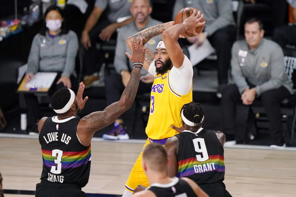 Los Angeles Lakers' Anthony Davis (3) is defended by Denver Nuggets' Torrey Craig (3) and Jerami Grant (9) during the first half of an NBA conference final playoff basketball game Thursday, Sept. 24, 2020, in Lake Buena Vista, Fla.