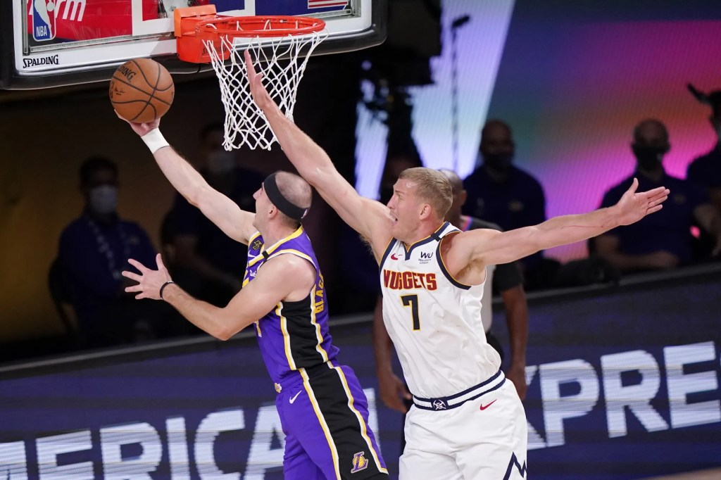 Los Angeles Lakers' Alex Caruso, left, shoots against Denver Nuggets' Mason Plumlee (7) during the first half of an NBA conference final playoff basketball game Saturday, Sept. 26, 2020, in Lake Buena Vista, Fla.