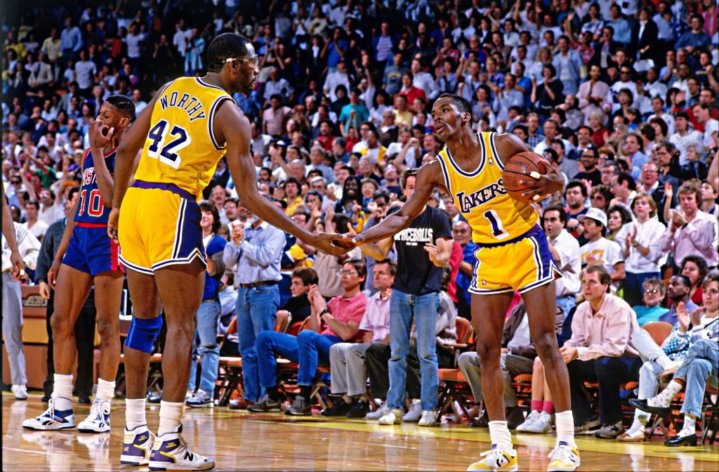 James Worthy #42 and Wes Matthews #1 of the Los Angeles Lakers high five during a game against the Detroit Pistons played circa 1988 at the Great Western Forum in Inglewood, California.