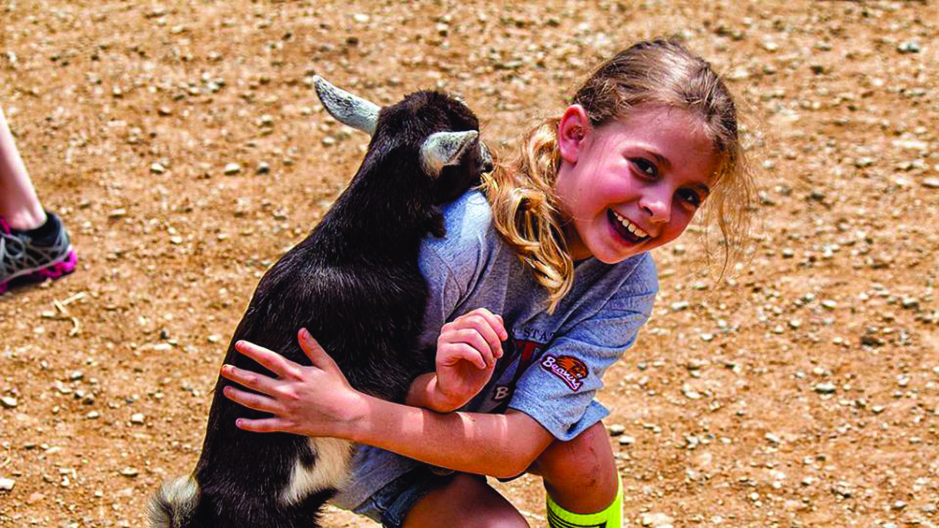Goat hugging girl at Lake Tobias Wildlife Park