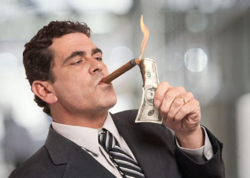 Hombre-rico-con-traje-encendiendose-un-puro-con-un-billete