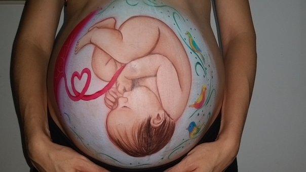 Pancia di donna con dipinto un bambino durante la gravidanza