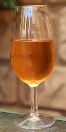 Fotografía de una copa llena de hidromiel de moras, donde podemos ver que tiene un color dorado rojizo brillante y transparenta.
