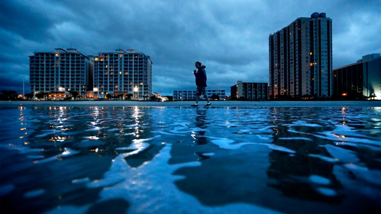 "Russ Lewis looks for shells along the beach as Hurricane Florence approaches Myrtle Beach, S.C., Friday, Sept. 14, 2018. ""We might get lucky we might not we'll find out,"" said Lewis of the storm. (AP Photo/David Goldman)"