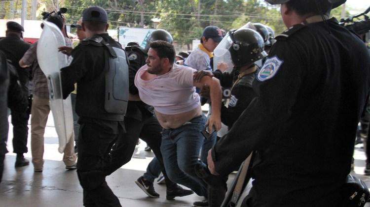 Un agente da policía de Nicaragua forcejea con el fotógrafo de AFP Luis Sequeira en medio de las detenciones de dirigentes opositores este sábado en Managua (Photo by Maynor Valenzuela / AFP)