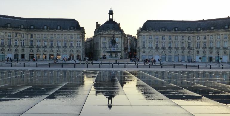 edificios de la plaza de la bolsa reflejados en el espejo de agua