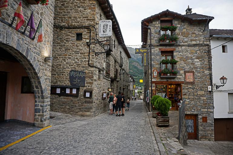 Calle empedrada de torla con edificios de piedra alrededor