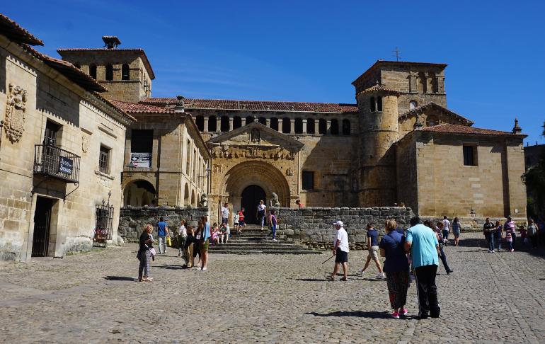 Es la colegiata de santa juliana de Santillana del mar. Es un edificio de piedra. En ella desembocan las dos calles principales del pueblo y hay como una placita con gente.
