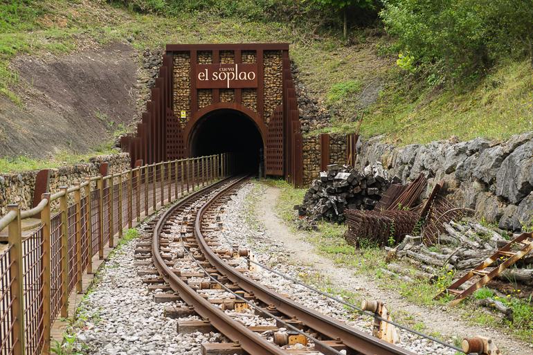 Entrada al túnel de la cueva de el soplao. Se ven las vías del tren por donde pasa el vagón de la visita turística