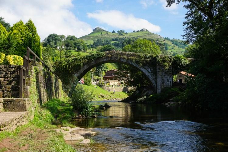"""Puente de piedra cubierto de vegetación. Por debajo para el río Mieres que no es muy caudaloso y por detrás del puente se ven 2 montañitas, las famosas """"dos tetas de liérganes"""". Este es otro de esos lugares que tenemos que ver en Cantabria"""