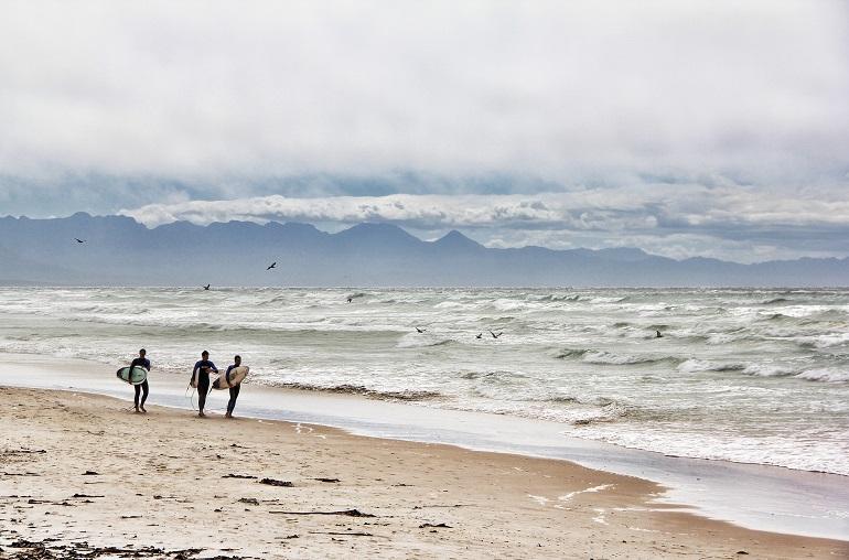 tres surferos caminando a orillas del mar