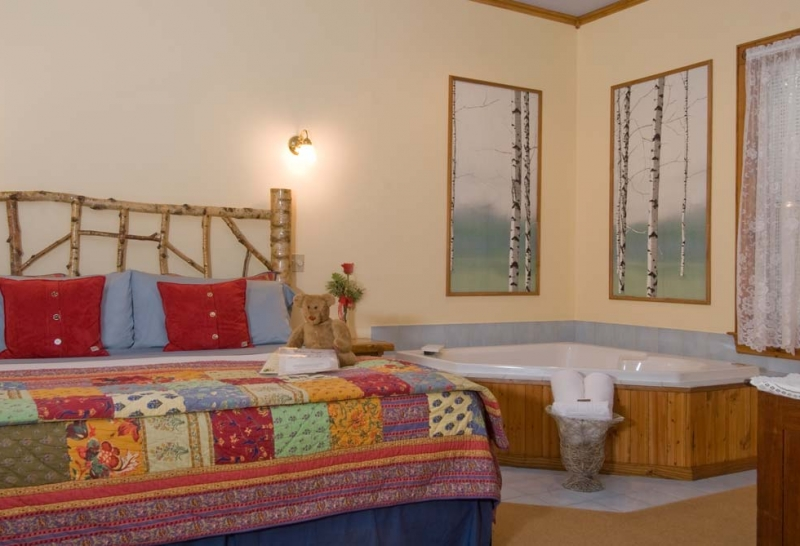 In Room Jacuzzi next to bed with colorful Quilt