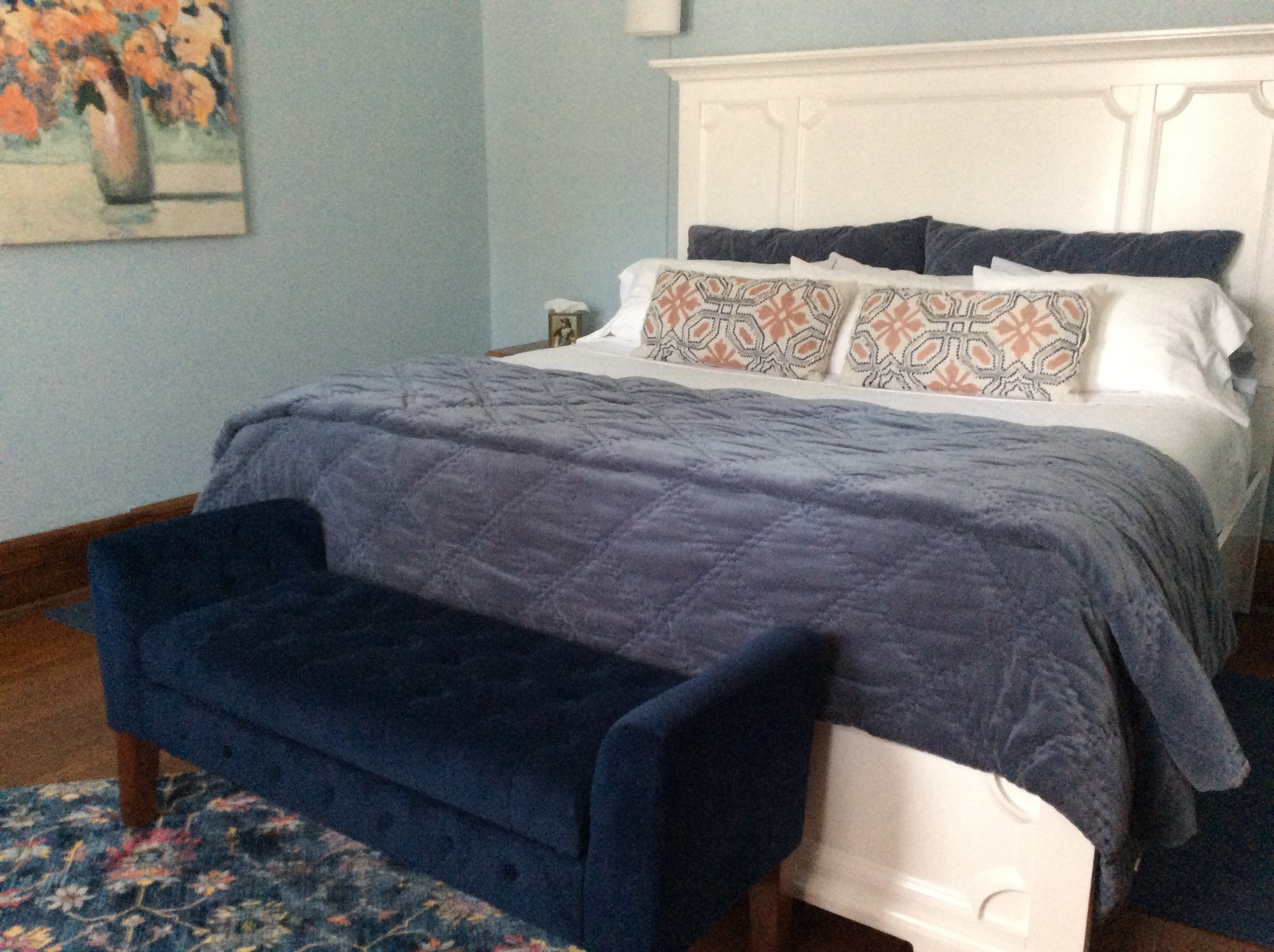 Large bed with white headboard and blue blanket