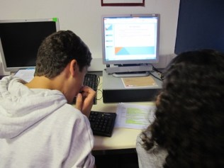 Two young people are sat at a computer. The picture shows the backs of their heads a