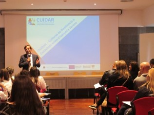 Man speaking in front of a screen with the CUIDAR logo and the text 'CUIDAR - Culturas de Resiliencia a Catastrofe entre Criancas e Jovens'